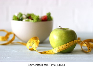 tape and lettuce on a light background. Slimming, diet, healthy food.