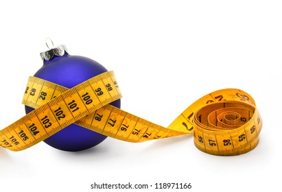 Tape measure around a bauble concept symbolizing Christmas weight gain from eating too much food.