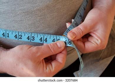 Tape measure around pregnant woman's waist