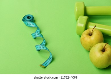 Tape measure in cyan blue color near barbells and juicy apples. Healthy life symbols. Diet and sport regime concept. Dumbbells in bright green color, twisted measure tape and fruit on green background