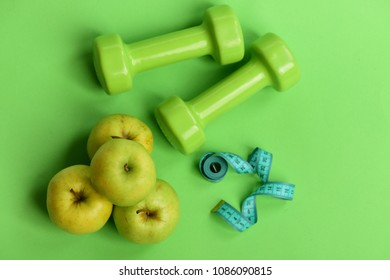 Tape measure in cyan color by barbells and juicy apples, topview. Diet and sport regime concept. Healthy lifestyle symbols. Dumbbells in bright color, rolled measure tape and fruit on green background