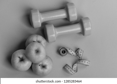 Tape measure in cyan color by barbells and juicy apples, topview. Healthy lifestyle symbols. Dumbbells in bright color, rolled measure tape and fruit on green background. Diet and sport regime concept