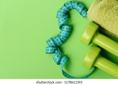 Tape measure in cyan color near lightweight barbells, copy space. Athletics and weight loss concept. Dumbbells in green color, twisted measure tape and towel on green background. Sports regime symbols