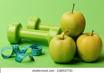 Tape measure in cyan color near barbells and juicy apples, close up. Dumbbells in bright color, measure tape and fruit pyramid on green background. Healthy regime symbols. Athletics and weight concept