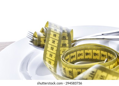 Tape measure with fork and spoon on a plate