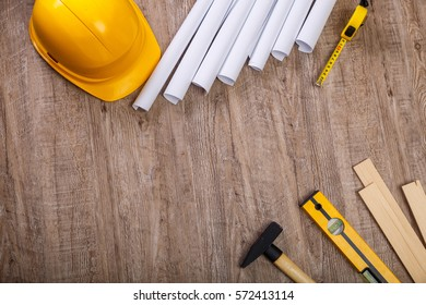 Tape measure, hammer and building level. Wooden planks and helmet. Paper plans. Wood rustic background.