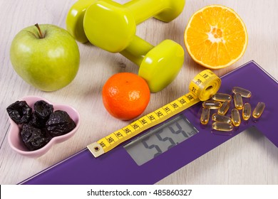 Tape measure on digital bathroom scale for weight of human body, dumbbells for fitness, fresh fruits and tablets supplements, concept of healthy lifestyle and slimming