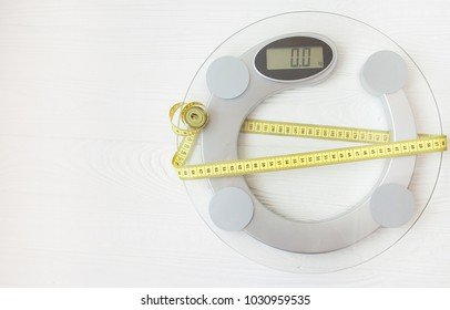 tape measure on a white scale, wooden surface on background, dieting and weight loss concept