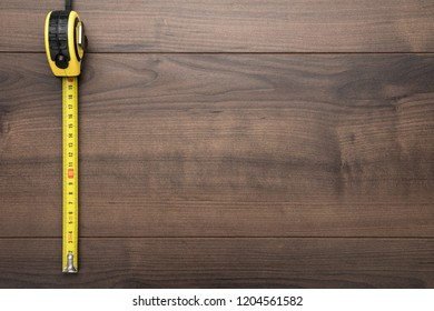 tape measure over wooden background with copy space. top view photo of yellow tape mesure on brown table