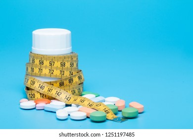 Tape measure and pills on a blue background