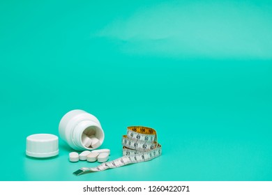 Tape measure and pills on a bright green background