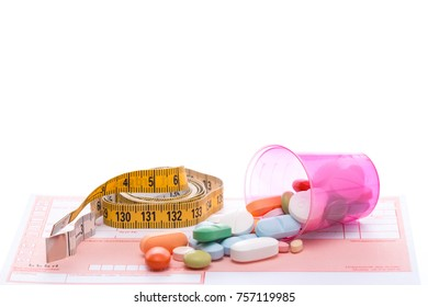 Tape measure and pills on a white table