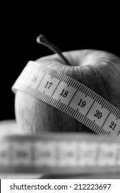 Tape measure wound around an apple in a black and white diet, health, weight loss and fitness concept with copyspace on a black background.