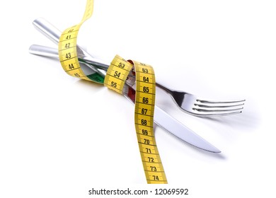 tape measure wrapped around knife and fork, white background