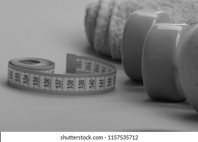Tape measure in yellow color near lightweight barbells, close up. Dumbbells in green color, twisted measure tape and towel on green background. Healthy regime equipment. Diet and sport regime concept