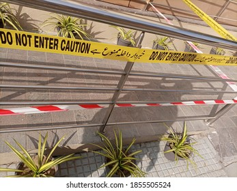 A tape prohibiting the entry at a crime scene. the warning is written in Urdu and English  - Shutterstock ID 1855505524