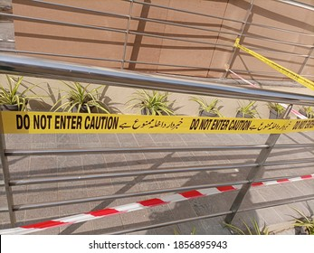 A tape prohibiting the entry at a crime scene. the warning is written in Urdu and English  - Shutterstock ID 1856895943