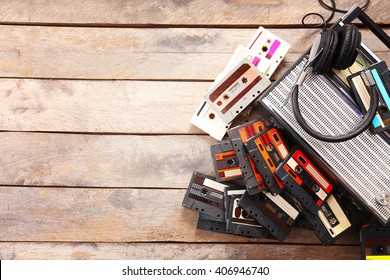 Tape recorder and retro cassette with headphones on wooden table, copy space