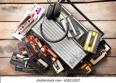 Tape recorder and retro cassettes with headphones on wooden table background
