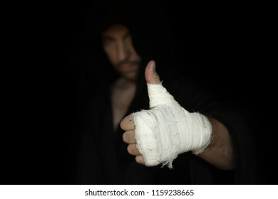 Taped fist of professional boxer. Boxer gesturing his thumb up. Boxing preparation before rumble.