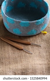 Tapestry crochet bag with crochet work on burlap background. Yarn and wood crochet needles.