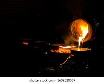 Taping molten iron into ingots at iron foundry
