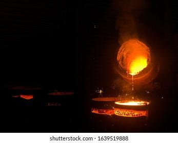 Taping molten ironinto ingots at iron foundry
