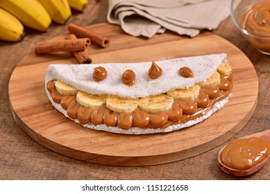 Tapioca filled with banana slices and dulce de leche on wooden cutting board