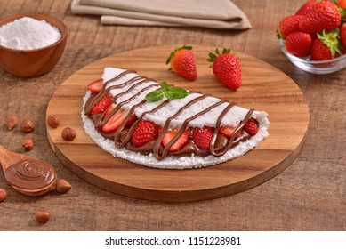 Tapioca filled with hazelnut cream and fresh strawberries on wooden background