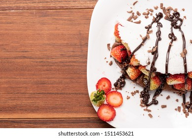 Tapioca filled with strawberries and chocolate on wooden background. Flatbread made from cassava (also known as casabe, bammy, beiju, bob, biju).