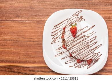 Tapioca filled with strawberries on wooden background. flatbread made from cassava (also known as casabe, bammy, beiju, bob, biju).
