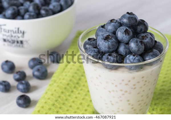 Tapioca pudding with fresh blueberries on the top. Sitting on a white wood table and a green cloth. White bowl of fresh blueberries in the background.