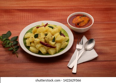 tapioca- seasoned tapioca / kappa puzhukku , tasty healthy south indian specially kerala food which is beautifully arranged in a white  plate with red fish curry as side dish on a wooden background