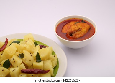 tapioca-seasoned tapioca / kappa puzhukku well garnished with dry chilli curry leaves and mustard placed on a white plate with tasty red fish curry as side dish on a white background