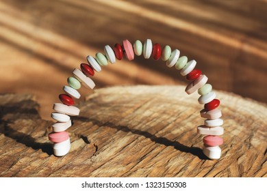Taplets pills addiction concept formed in arch on natural wooden background with sun flares