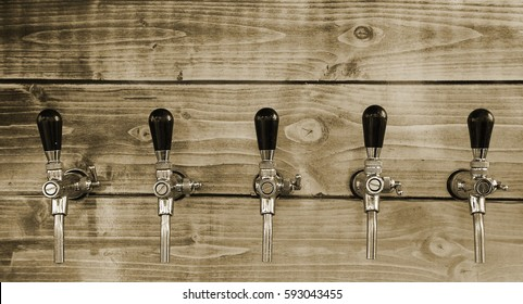 taps for beer bottling and other drinks on wooden background