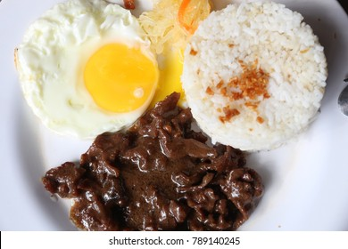 Tapsilog breakfast - typical morning food in Philippines. Garlic rice, fried egg and cured beef tapa.
