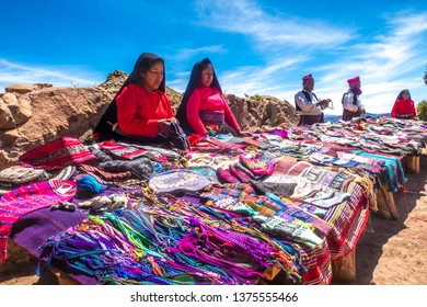 Taquile island / Peru - 11 04 2018: Local women selling traditional textiles