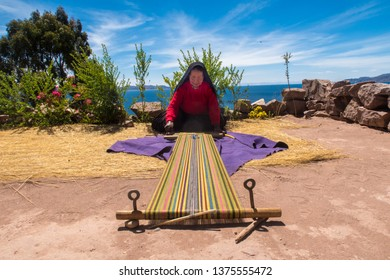 Taquile island / Peru - 11 04 2018: Local woman weaving traditional textiles
