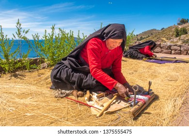 Taquile island / Peru - 11 04 2018: Local women weaving traditional textiles