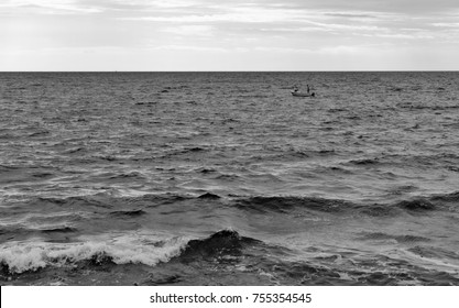 TAR, CROATIA - SEPTEMBER 21, 2017: Two unrecognized men in a motor boat are preparing to dive in the stormy Adriatic Sea. Black and white.