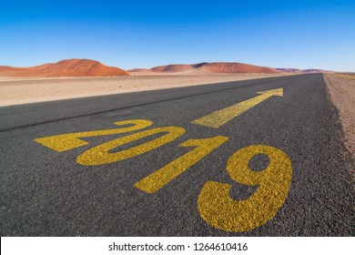 tar road in the Namib desert with the word 2019 and an yellow arrow showing forward to the horizon, business concept for turn of the year; Namibia, Africa