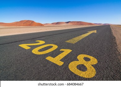 tar road in the Namib desert with the word 2018 and an yellow arrow showing forward to the horizon, business concept for turn of the year; Namibia, Africa