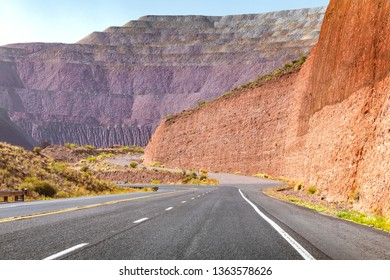 Tar road surrounded with dramatic minefield landscape.