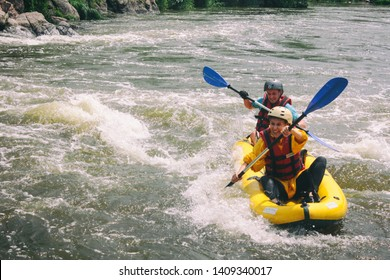Tara, Montenegro - June 14 2018: Young couple enjoy white water kayaking on the river, extreme and fun sport at tourist attraction.  Active adventure couple along the river