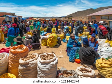 TARABUCO, BOLIVIA - OCTOBER 14, 2018: A group of indigenous men and women in traditional clothing with special hair styles and hats as well as colorful textiles in Tarabuco near Sucre, Bolivia.