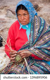 Tarahumara woman sitting outdoors and weaving pine-needle baskets. March 03, 2010 - Copper Canyon - Sierra Madre, Chihuahua State, Mexico, South America