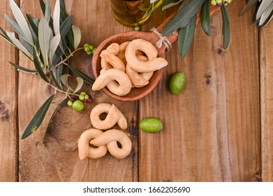 Taralli is a traditional Italian snack food typical of Puglia regional cuisine. Tarallini with fresh olive branches on a wooden table. Copy space. Above.