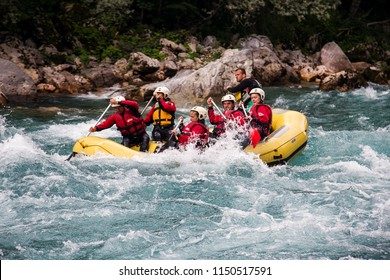 Tara,Montenegro - June 27.2018 -  Rafting on a magic river. Waves with spray and foam crashing on the side of the boat, and people rowing oars. Extreme sport.