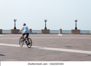 "Taranto, Italy - August 15, 2015: Cyclist walks through the square ""La Rotonda"", in the background of the streetlights, was used the photographic technique of the long exhibition."